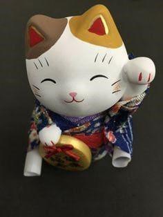 Chú mèo thần tài trong bộ trang phục truyền thống với biểu cảm thích thú